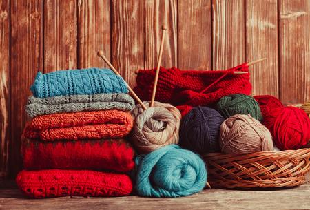 moda ropa: Hilos de colores, agujas de tejer y ropa en la mesa de madera Foto de archivo