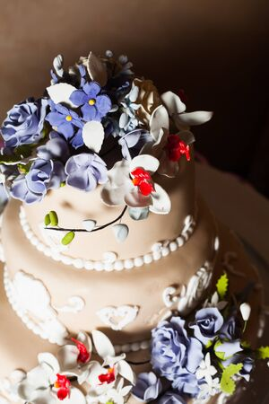 nuptial: Three-storied wedding cake with violet flowers on a glass stand Stock Photo