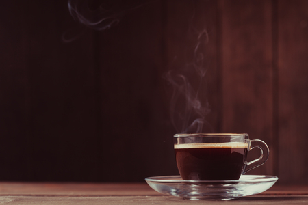 Cup of coffee with fume on the wooden background