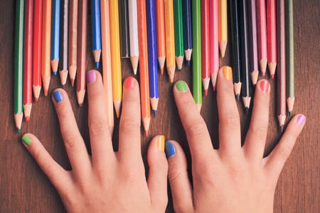 multicoloured: Color rainbow pencils in teenagers hands with multicoloured nails