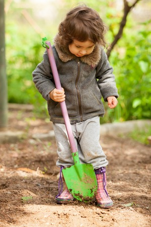tried: Little girl in rubber boots holding a shovel and tried to dig