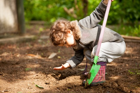 dig: Little girl in rubber boots holding a shovel and tried to dig