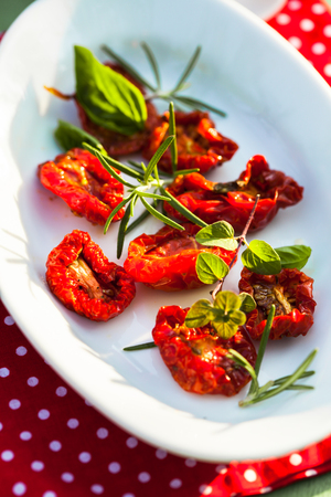 olive: sun dried tomatoes on a white plate with fresh herbs - rosemary, basil and oregano