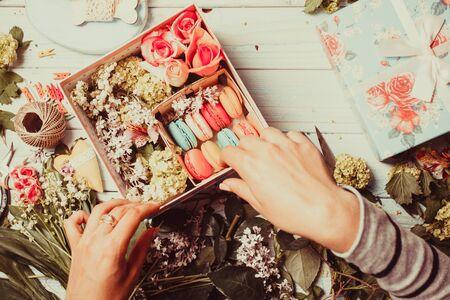 mujer con rosas: Preparaci�n de la caja de la flor con macarrones, vista desde arriba del lugar de trabajo del florista