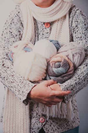 warmly: Warmly dressed woman holding a basket of balls woolen yarn