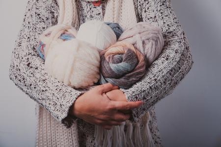 warmly: Warmly dressed woman holding a basket of balls woolen yarn