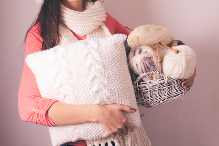 warmly: Warmly dressed woman holding a white knitted pillow Stock Photo