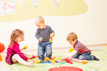 Three kids  playing in the playroom. Children fantasize that they Musicians. Girl plays the drums, the first boy playing the xylophone, the second boy playing the piano.