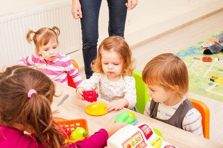 housewares: Children playing with housewares and artificial fruit in kindergarten Stock Photo
