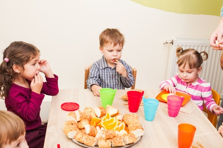 children hands: Children are sitting at the table with lunch and eating fruits and cakes Stock Photo