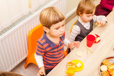 children eating: Children are sitting at the table with lunch and eating fruits and cakes Stock Photo
