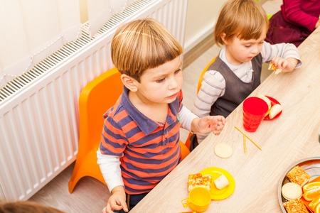 niños sentados: Los niños están sentados en la mesa con la comida y comer frutas y tortas Foto de archivo