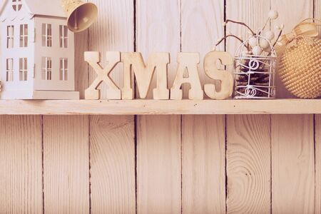 christmas shopping: Christmas decor on the shelf - wooden letters XMAS over wooden wall Stock Photo