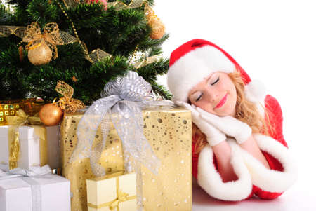 santa girl: Daydreamed christmas santa girl with gifts and decorated fir-tree. Stock Photo
