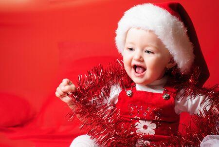 gestos de la cara: Little santa girl looks and sitting on the red cloth