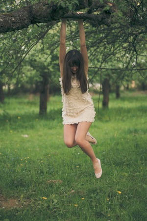 hangs: Pretty girl playfully hangs on a tree branch with bent legs Stock Photo