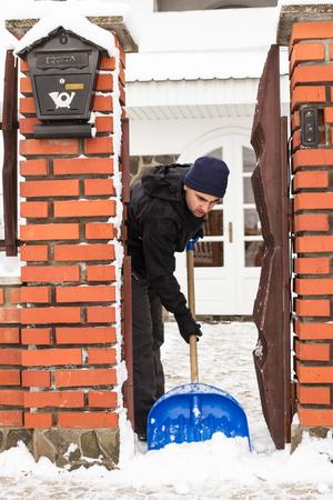 suburban: Young man remove snow near the suburban house