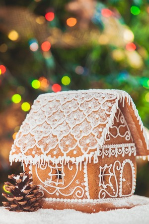 christmas scene: gingerbread house over defocused lights of Chrismtas decorated fir tree