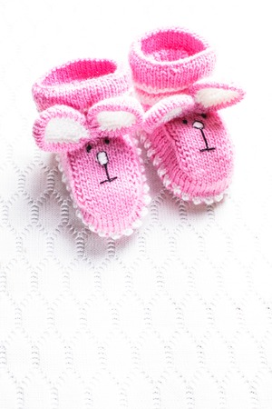 booties: Knitted pink baby booties with rabbit muzzle over textile background
