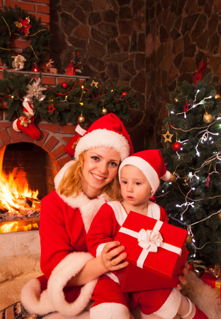 fireplace family: Mother and son are sitting near fireplace and christmas tree. Family look into a gift box.