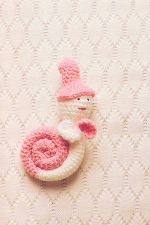 escalera de caracol: Knitted white with pink snail hung on the wall