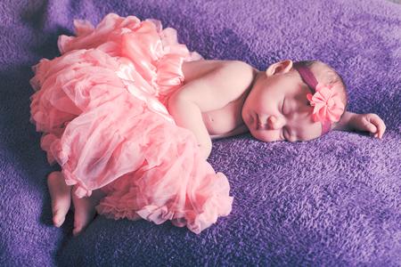 cute flowers: Newborn pretty baby girl in pink tutu dress sleeps on the purple textile Stock Photo