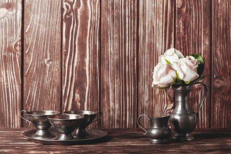 grunge flatware: Still life with antique  plate and flowers in tin jug