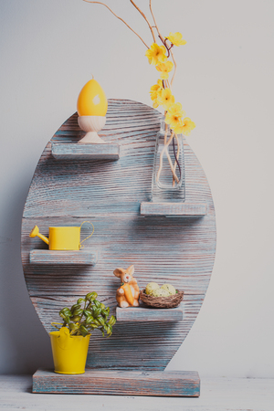 watering pot: Grey easter shelf with miniature buckets, yellow watering pot, colored eggs and  rabbits isolated on white. Spring and Easter decor