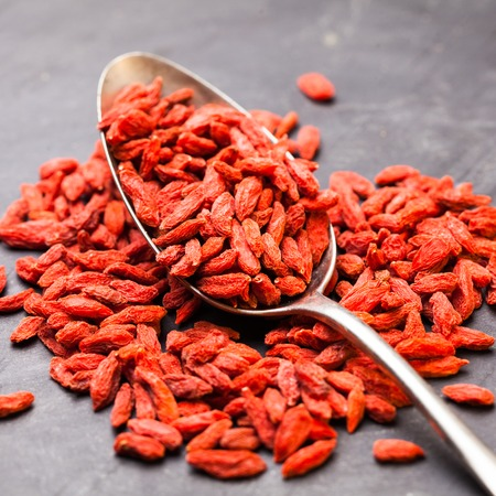 superfruit: Steel tablespoon of red dried goji berries on a dark background Stock Photo