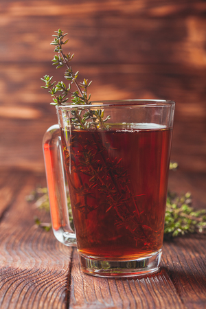 water thyme: Fragrant herbal tea with bunches thyme in a glass mug