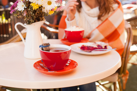two girls: Woman is sitting in cafe outdoor and eat cake and cocoa, cozy autumn