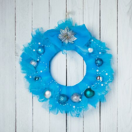 guipure: Christmas wreath from blue guipure on white wall Stock Photo