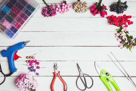 tijeras: Plastic berries, flowers, beads and instruments for doing handmade decorations and bijouterie. Top view Foto de archivo