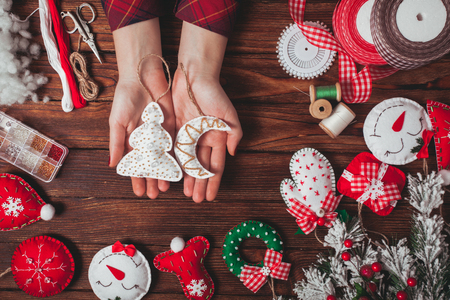 tree decorations: felt Christmas decorations on the wooden table - woman is preparing for handmade