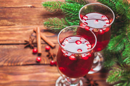 stick of cinnamon: Glass of mulled wine with cranberry and scented cinnamon sticks on a wooden table