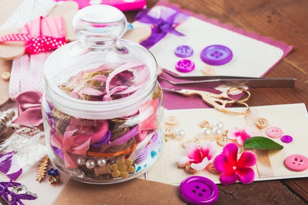 brads: Scrapbooking craft materials in a glass bottle Stock Photo