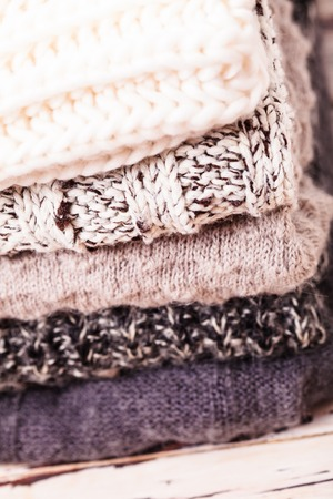 Stack warm knitted sweaters in white and gray shades Stock Photo