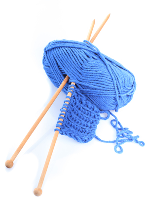 Knitting close up with blue woven thread isoalated on white Stock Photo