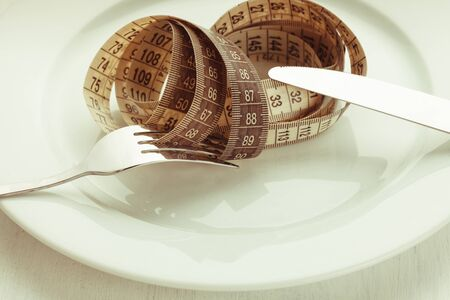 wooden metre: Fork and knife with meter on the empty white plate, diet concept