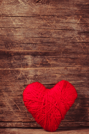 hilo rojo: Red thread heart over old shabby background. Valentine concept