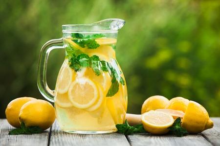 limonada: Preparación de la bebida limonada. Limonada en la jarra y los limones con la menta en la mesa al aire libre Foto de archivo