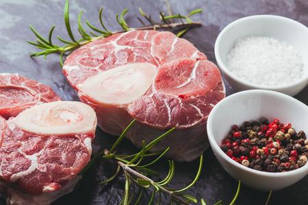 十字のスレート板のカットの仔牛すね肉の生の新鮮なスライス