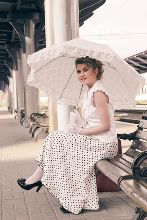 railroad station: Woman in vintage dress with old suitcase on the railroad station Stock Photo