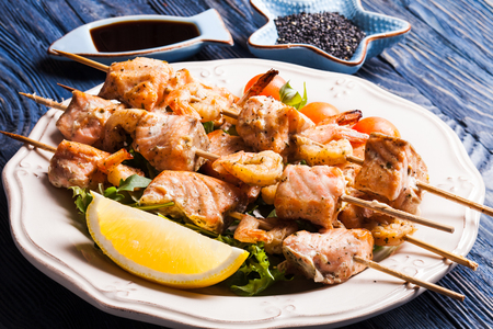Seafood shashlik - slices of salmon and shrimps on a wooden skewers