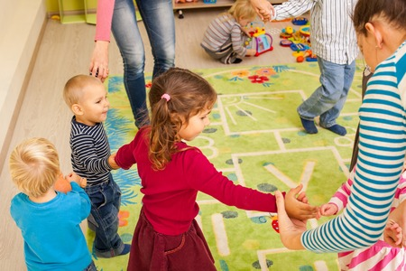 jointly: Group of little children dancing holding hands and enthusiastically watching the boy, who laughs with joy