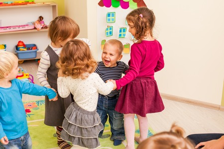 enthusiastically: Group of little children dancing holding hands and enthusiastically watching the boy, who laughs with joy