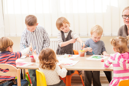 educator: Children and tutor are painting with a brush and watercolors on paper in the kindergarten