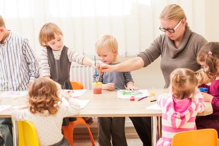 gente sentada: Los ni�os y profesor particular est�n pintando con un pincel y acuarelas sobre papel en el jard�n de infantes