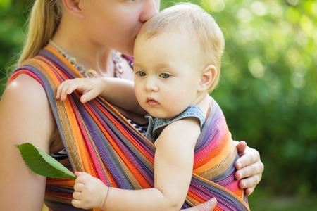 madre y bebe: Bebé en honda al aire libre. Madre está llevando a su hijo y que muestra detalles de la naturaleza Foto de archivo