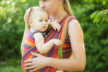 physiologic: Baby in sling outdoor. Mother is carrying her child and showing nature details Stock Photo